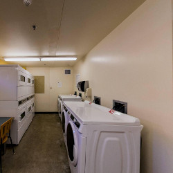 A laundry room with front and top loading machines.
