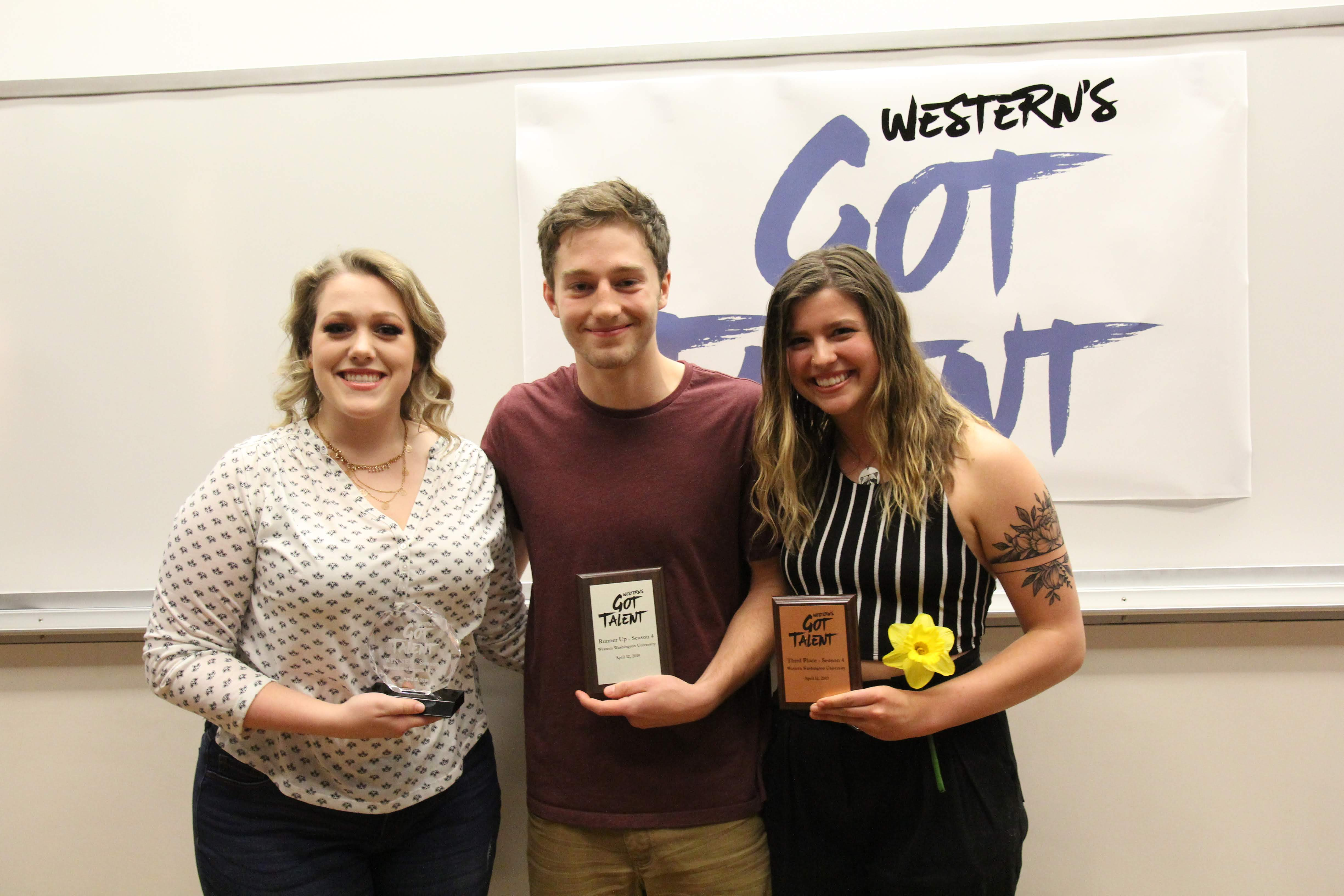 3 people smiling and holding awards